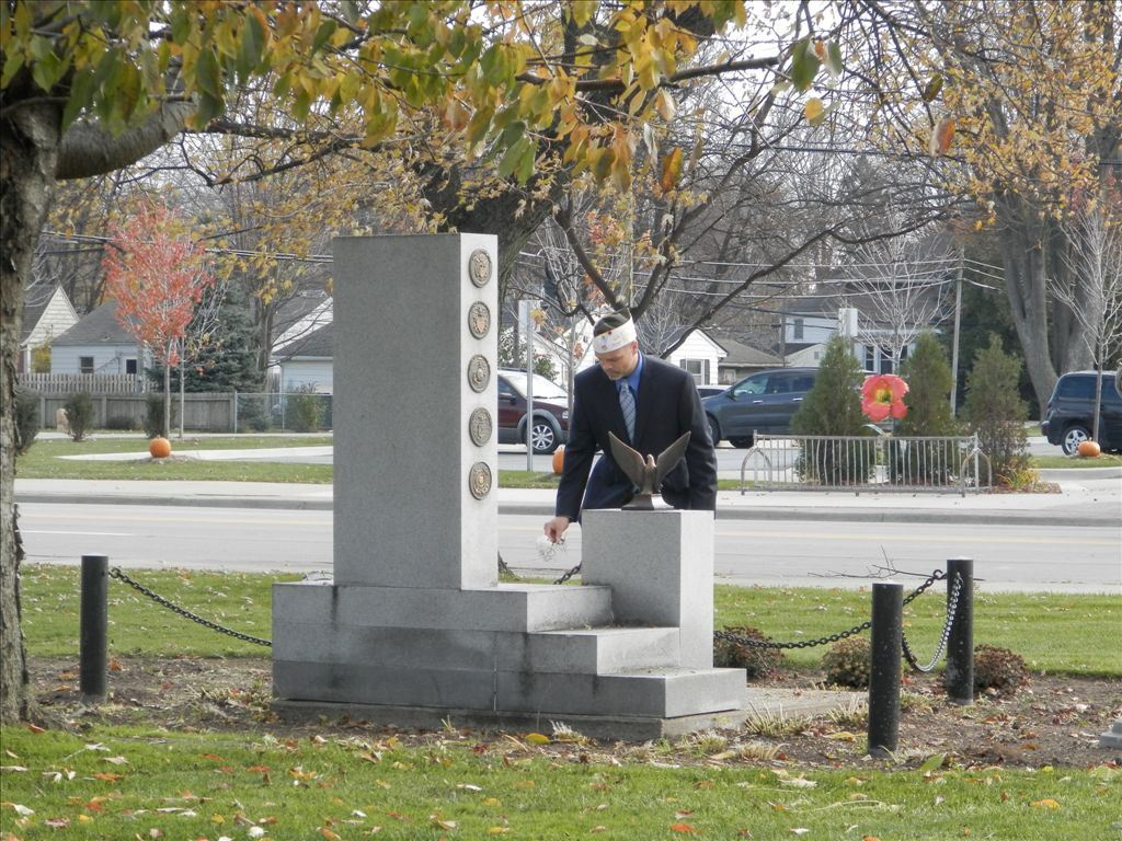 A veteran places a flower on the memorial