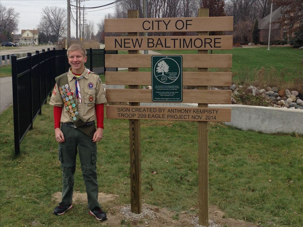 Boy Scout standing by the City of New Baltimore sign